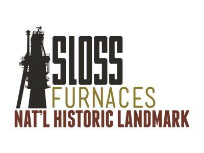 Furnace next to text of Sloss Furnaces National Historic Landmark
